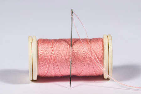 threaded: Threaded needle in a pink spool