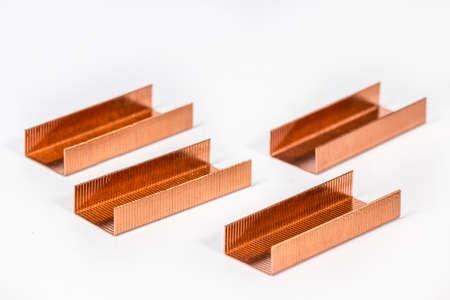 metal fastener: Piles of copper staples on white