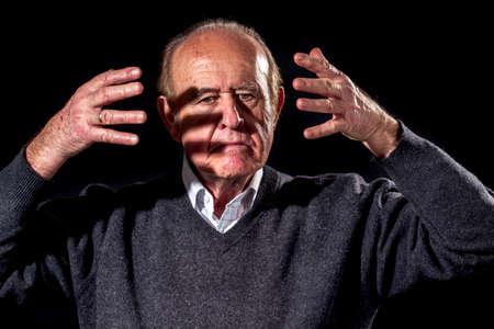 outburst: Senior man has an angry outburst, on black background