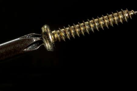 screwing: Screwing a golden screw, on black background