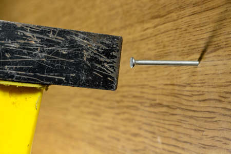 hammering: Hammering a nail into a wooden surface with a yellow handle hammer