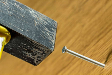metal fastener: Detail of hammer and nail on wood Stock Photo
