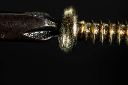 screwing: Screwing a golden screw, on black