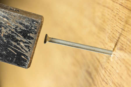 metal fastener: Hammering a wire nail into a wooden surface