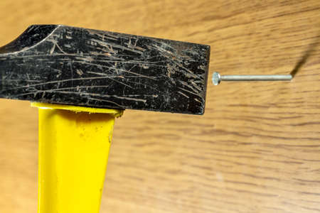 wire pin: Nailing a wire nail into a wood board with a yellow handle hammer