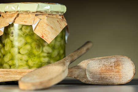 conserved: Several wooden spoons beside a bottle of baby broad beans, fried and conserved in Extra Virgin olive oil. Delicatessen.
