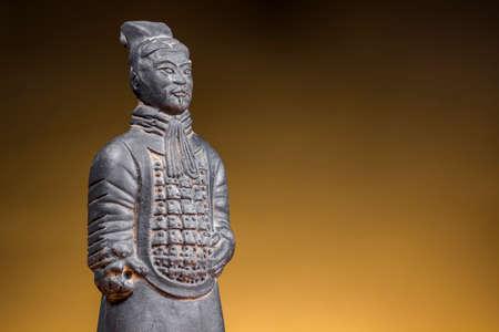sol naciente: Ancient chinese warrior on rising sun background. Terracotta figurine.