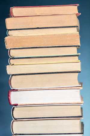 pedagogic: Top of a pile of books, on textured blue background. Stock Photo