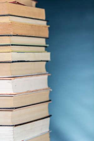 Vue latérale d'une pile de livres, sur fond bleu texturé. Espace libre à droite