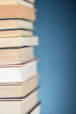 Vue détaillée d'une pile de livres, sur fond bleu texturé. Espace libre à droite