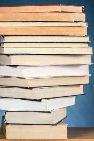 Pile de livres placés par étapes sur une grille en bois, sur fond bleu texturé