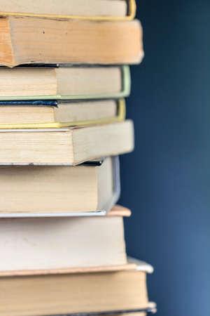 Vue détaillée d'une pile de livres, sur fond bleu texturés.