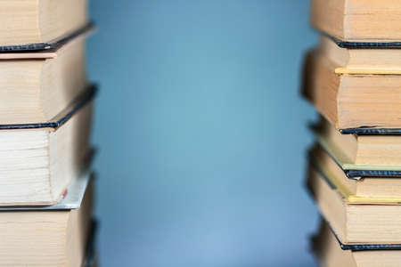 Detail view of two piles of books, with clear space at center. On blue background