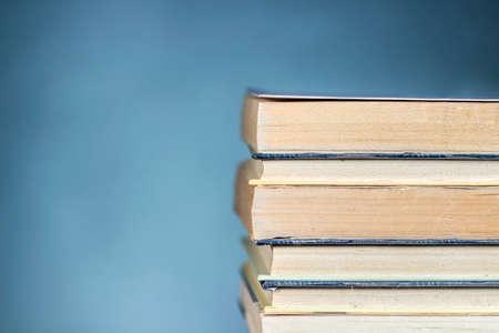 Vue détaillée de plusieurs livres empilés, sur fond bleu dégradé. Effacer l'espace à gauche et en haut