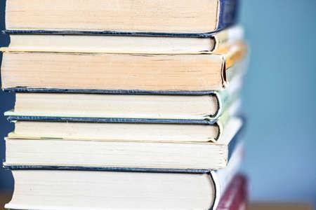 Vue rapprochée de la pile de livres, sur fond bleu.