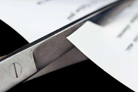 folio: Detail of scissors cutting a paper, on black