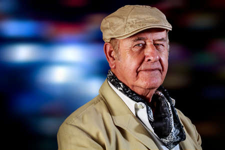 Senior man with hat and neckerchief greets to camera while walks, with street lights at background