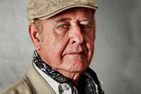 Primer plano de hombre de edad avanzada con los ojos verdes que lleva un sombrero y un pañuelo para el cuello, delante de la pared encalada