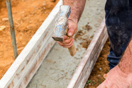 footing: Detail of builders hand while is adjusting the bricklayers rulers with a hammer