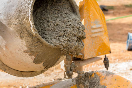 substructure: Pouring mortar from the cement mixer into a wheelbarrow. Building work