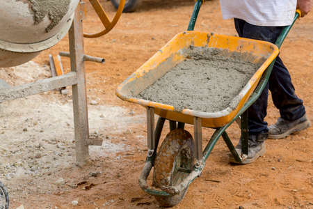 footing: Builder is carrying a wheelbarrow with mortar to fill the foundations of a wall Stock Photo