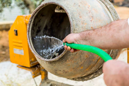 substructure: Worker is washing a cement mixer with a green hose pipe Stock Photo