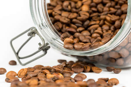 Roasted coffee beans get out of overturned glass jar, on white