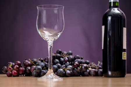 rioja: Wine glass in front of red grapes and Rioja wine bottle, with purple background Stock Photo
