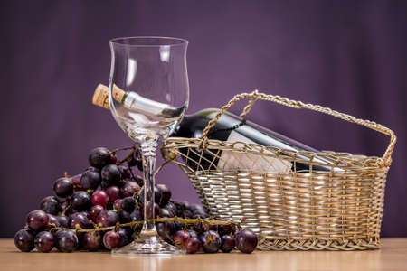 Empty stemware beside a cluster of red grapes and a red wine bottle in a tabletop wine rack