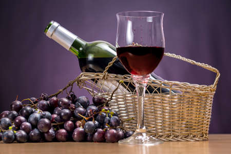 Wine glass with Rioja beside red grapes and open bottle into a tabletop wine rack, with purple background
