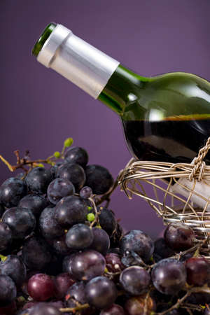 spirituous beverages: Red grapes beside a bottle of red wine, on purple background