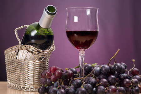 spirituous beverages: Glass and bottle of Rioja wine beside red grapes, on purple background