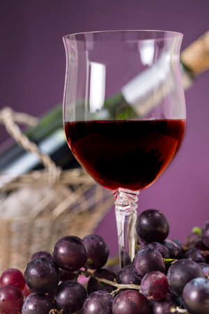 oenology: Wine glass of Rioja beside grapes, in front of a bottle of wine