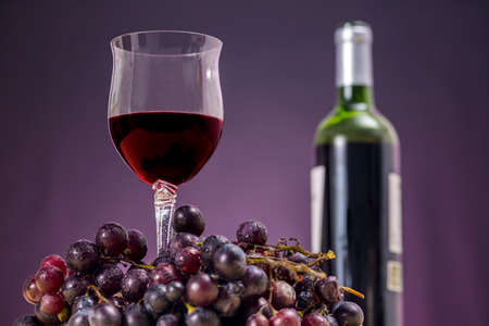 Glass of Rioja wine beside red grapes, in front of a wine bottle