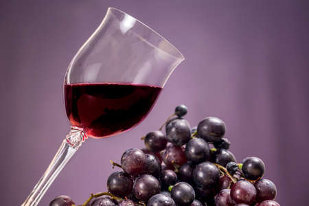 oenology: Cup of red wine beside red grapes, on purple background Stock Photo