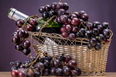 Open bottle of Rioja red wine into a tabletop wine rack, with clusters of red grapes Stock Photo
