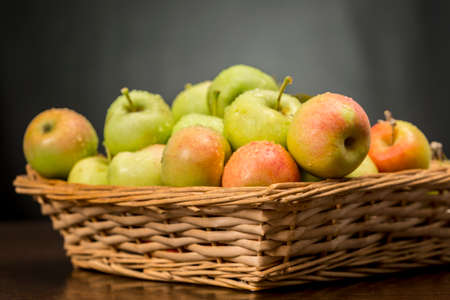 Sevillian apples into a wicker basket, traditional variety of delicious sweet fruits with green and red skin