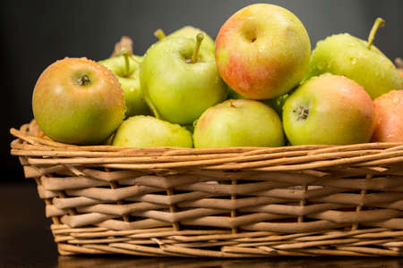 larder: Little apples with green and red skin into a wicker basket. Traditional variety of apples originating from Andalusia