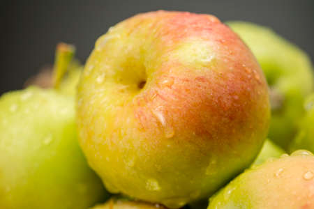 Close-up of a heap of Sevillian apples, traditional variety of small fruits with a delicious sweet flesh, but acid skin (red and green coloured)  Stock Photo