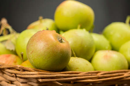 Heap of sevillian apples into a wicker basket. Traditional variety of small and delicious apples