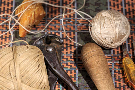 Leather needle beside waxed thread and hand tools used by shoemakers