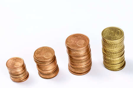 Different eurocent coins stacked in columns, on white. Blank space at top