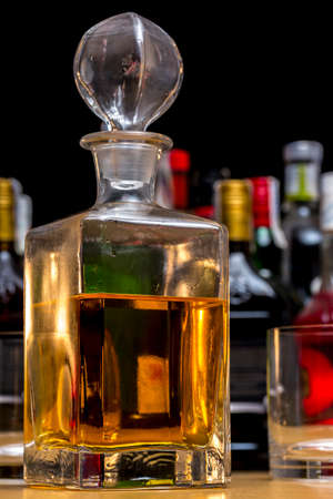 Square glass bottle of malt whiskey in front of several bottles of different alcoholic drinks Stock Photo