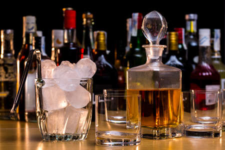 Whisky bottle beside a ice bucket and empty glasses in front of different liquors Stock Photo