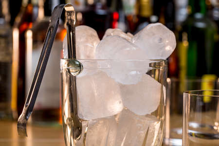Close-up of tongs and glass ice bucket full of ice cubes, in front of whiskey and other alcoholic drinks