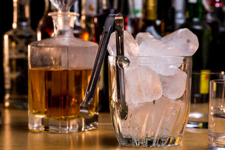 Glass ice bucket full of ice cubes in front of whiskey and other alcoholic drinks Stock Photo