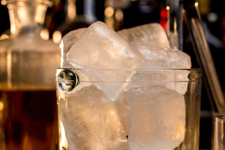 Cube ices into a glass ice bucket,  in front of whisky and other alcoholic drinks Stock Photo