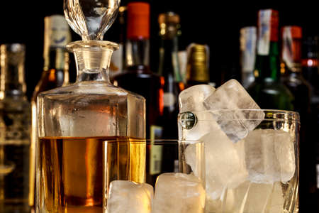 Scotch bottle beside ice bucket and glass with ice cubes, in front of different alcoholic drink bottles. On black