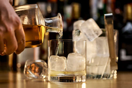 Barman is serving a good whiskey on the rocks Stock Photo