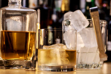 Whisky on the rocks beside square bottle and ice bucket Stock Photo